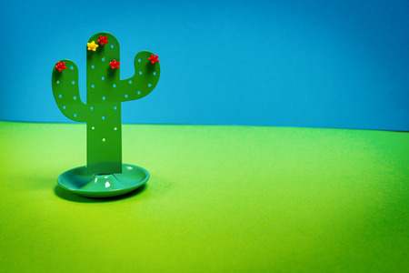 minimalistic colorful holiday background with a small toy cactus Imagens