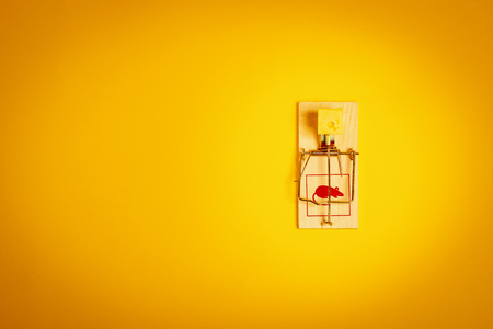 minimalistic yellow background with a mousetrap and a piece of tasty cheese