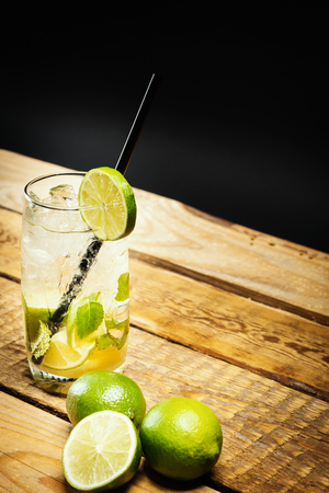 glass of delicious mojito on a wooden table with pieces of lime and mint leaves on a black background 스톡 콘텐츠