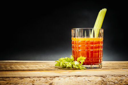 juicy red drink bloody mary with a piece of green celery on a wooden table