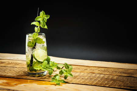 glass of delicious mojito with lime and mint leaves on a wooden table on a black background