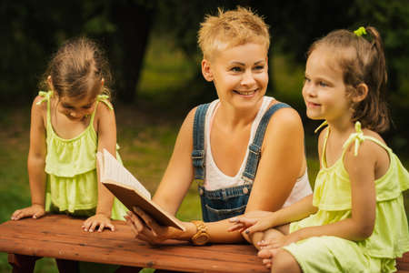 beautiful mother and two adorable daughters in dresses posing on a picnic table in a summer forest