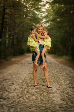 beautiful mother and two adorable daughters in dresses posing on the road in the summer forest