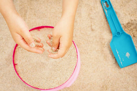 hands of a girl with sand over a colored bucket and shovel on the beach in summer
