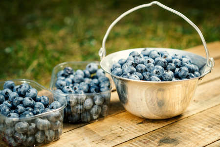 Juicy and blueberries in a container on an old wooden table in the summer Standard-Bild
