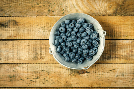 Juicy and blueberries in a container on an old wooden table in the summer Reklamní fotografie