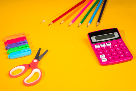 yellow school background with a crayons, calculator, ruler and felt-tip pens 版權商用圖片