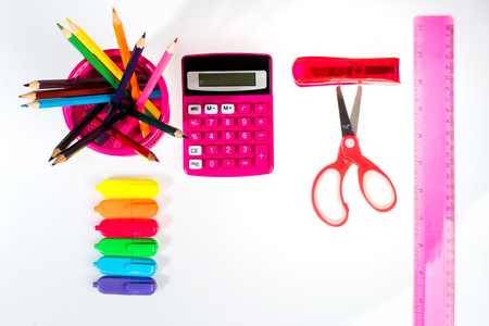isolated white school background with a pencil, calculator, ruler and felt-tip pens