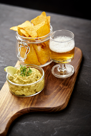 beer and a bowl of guacamole with nachos on an old black wooden table in a pub
