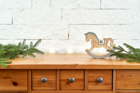 Christmas decoration with twigs of spruce and wooden horse on the old shelf on the background of a white brick wall