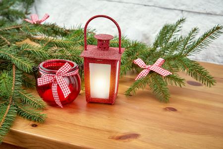 Decoración de Navidad con ramitas de abeto y un farolillo rojo en un estante antiguo en el fondo de una pared de ladrillo blanco.