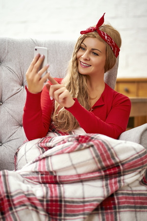 young smiling beautiful woman sitting in an armchair with a phone wrapped in a blanket during Christmas time Stock fotó