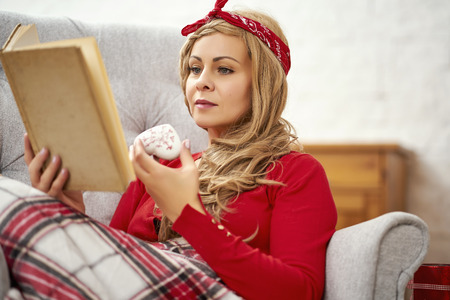 young beautiful woman sitting and reading a book and drinking tea in an armchair wrapped in a blanket during Christmas time