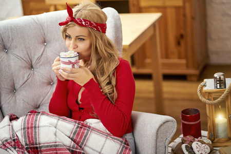 young smiling beautiful woman in armchair with a cup of hot chocolate wrapped in a blanket during Christmas time Stock Photo
