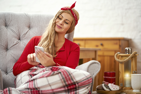 young smiling beautiful woman sitting in an armchair with a phone wrapped in a blanket during Christmas time Stock Photo