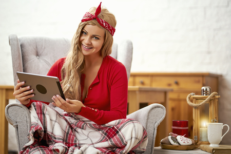 young smiling beautiful woman sitting in an armchair with a tablet wrapped up in a blanket during Christmas time Stock Photo