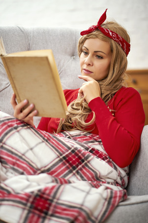 young smiling beautiful woman sitting and reading a book in an armchair at a coffee table with gingerbreads and candles wrapped in a blanket during Christmas time