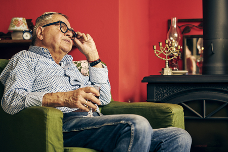 Pensive Jewish senior sitting in the armchair and drinking kosher wine
