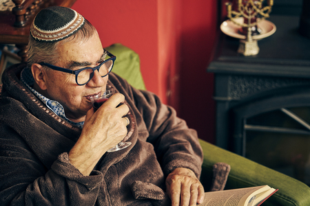 Jewish senior with glasses sitting in the armchair reading a torah book and drinking kosher wine