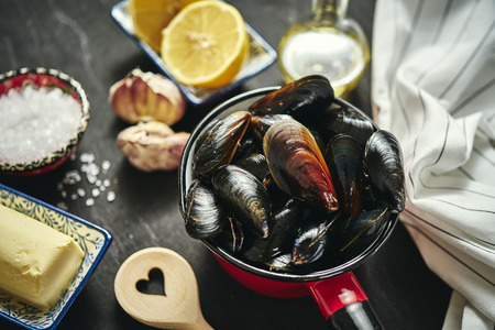 fresh, delicious raw mussels in a saucepan with butter, garlic, parsley, lemon and salt
