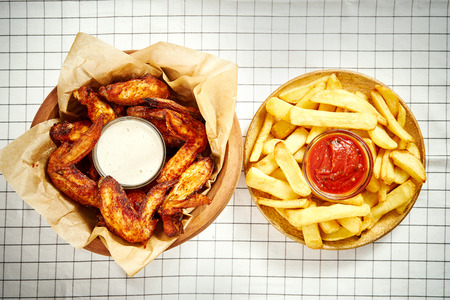 top view of delicious fried chicken wings, french fries and sauces on checkered tablecloth