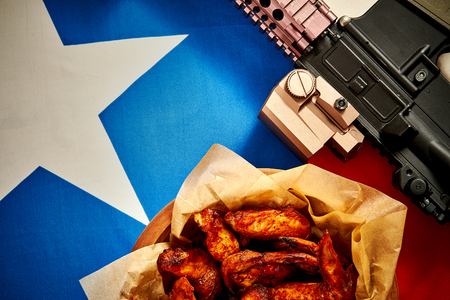 top view of delicious fried chicken wings and machine gun against texas flag background