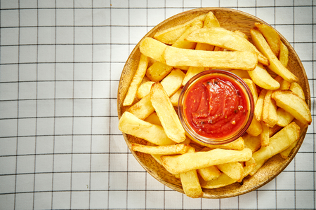 top view of delicious french fries on wooden plate with sauce on checkered tablecloth