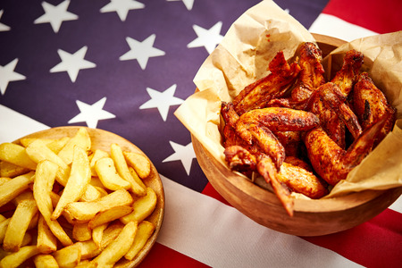 delicious fried chicken wings and french fries with background of the USA flag