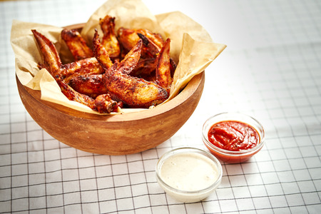 delicious fried chicken wings in a wooden bowl on a checkered tablecloth