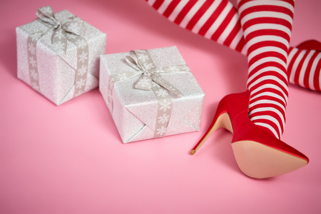 sexy santa woman's legs on a bright pink background and Christmas gifts