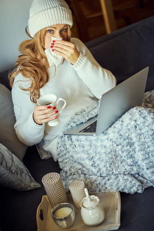 sick young beautiful blonde on a gray sofa with a blanket and laptop and a mug of tea Stockfoto