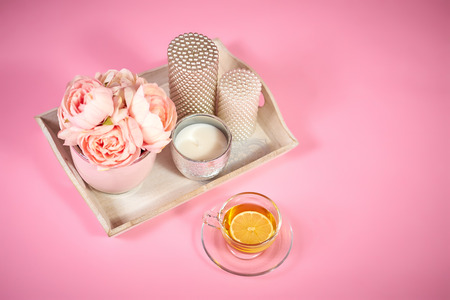 flowers peonies, candles on a wooden tray and tea on a light pink background