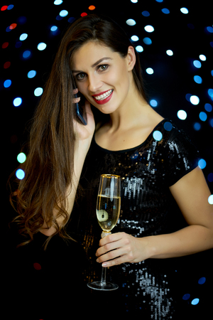 beautiful young smiling woman with one glass of champagne on a black background in New Year's Eve