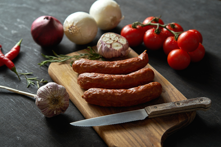 three delicious sausages with different vegetables on a wooden board, knife on a black table