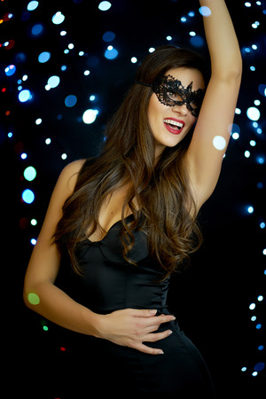 beautiful young smiling woman in a sexy face mask on a black background in New Year's Eve