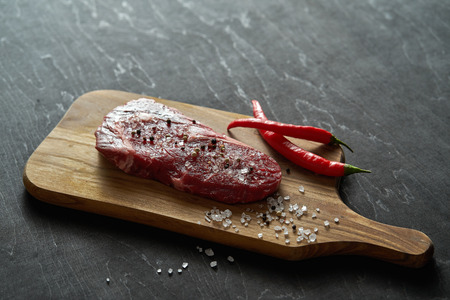 one raw piece of steak with salt, pepper on a wooden board with a chili pepper on a black table Фото со стока