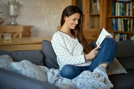 beautiful young brunette woman reading a book on a gray sofa. 스톡 콘텐츠