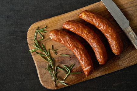 top view of three delicious sausages with a sprig of rosemary on a wooden board and knife on a black table