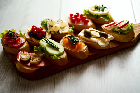 wooden board with colorful healthy mini sandwiches or tapas on a wooden table 免版税图像