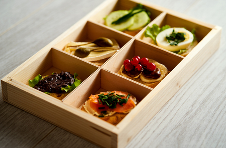 box with a set of healthy colorful mini sandwiches or tapas with vegetables and fish on a table