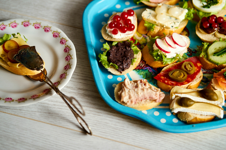 old blue tray with a set of healthy tapas or mini sandwiches with food tongs on a wooden table Standard-Bild