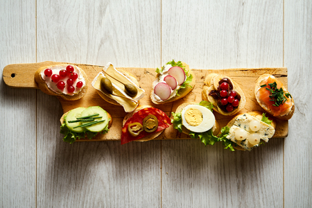 wooden board with colorful healthy mini sandwiches or tapas on a wooden table 스톡 콘텐츠
