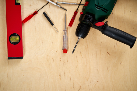 pattern background of various screwdrivers and a drill with a spirit level on  wooden work table
