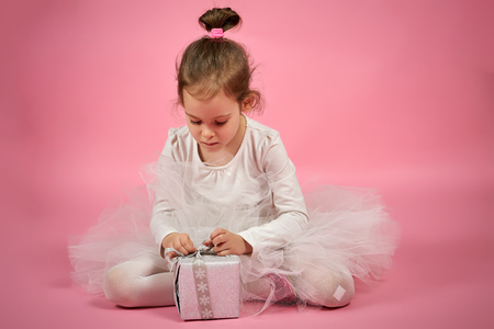 Cute little girl in tulle skirt opens a gift on a pink background