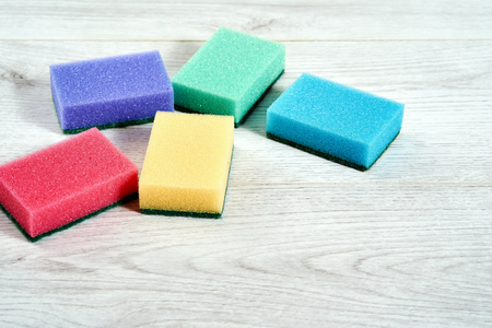 set of different colorful sponges for cleaning on light  background