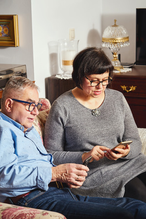 marriage senior couple surfing the net with mobile phone while sitting on the sofa.