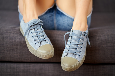 View of sexy female legs in jeans shorts and blue sneakers on a gray couch.