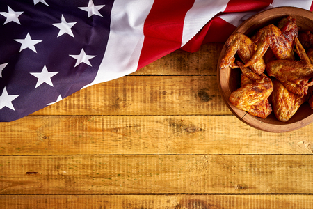 Top view of delicious grilled chicken wings in wooden bowl and the flag of America on wooden table.