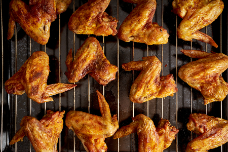 Delicious hot grilled chicken wings on grid grill.