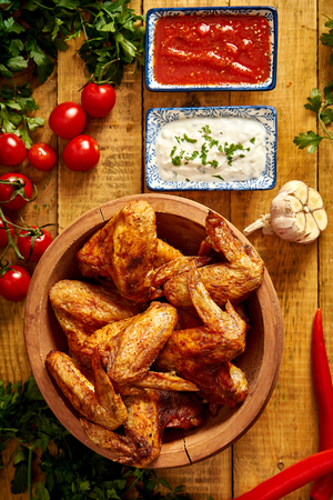 Delicious grilled chicken wings in bowl with spices and vegetables with dips on wooden table. Фото со стока